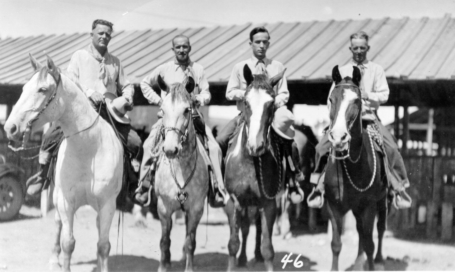 Black-and-white photo of four men on horseback.