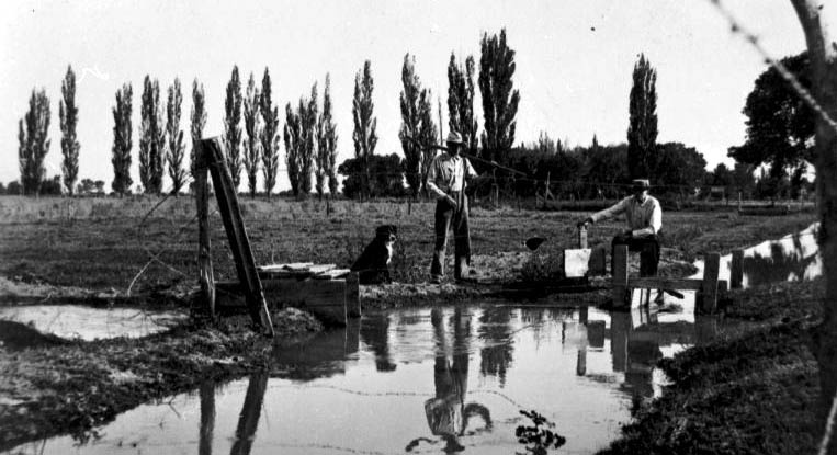 Black-and-white photo of two men and a dog at a canal.