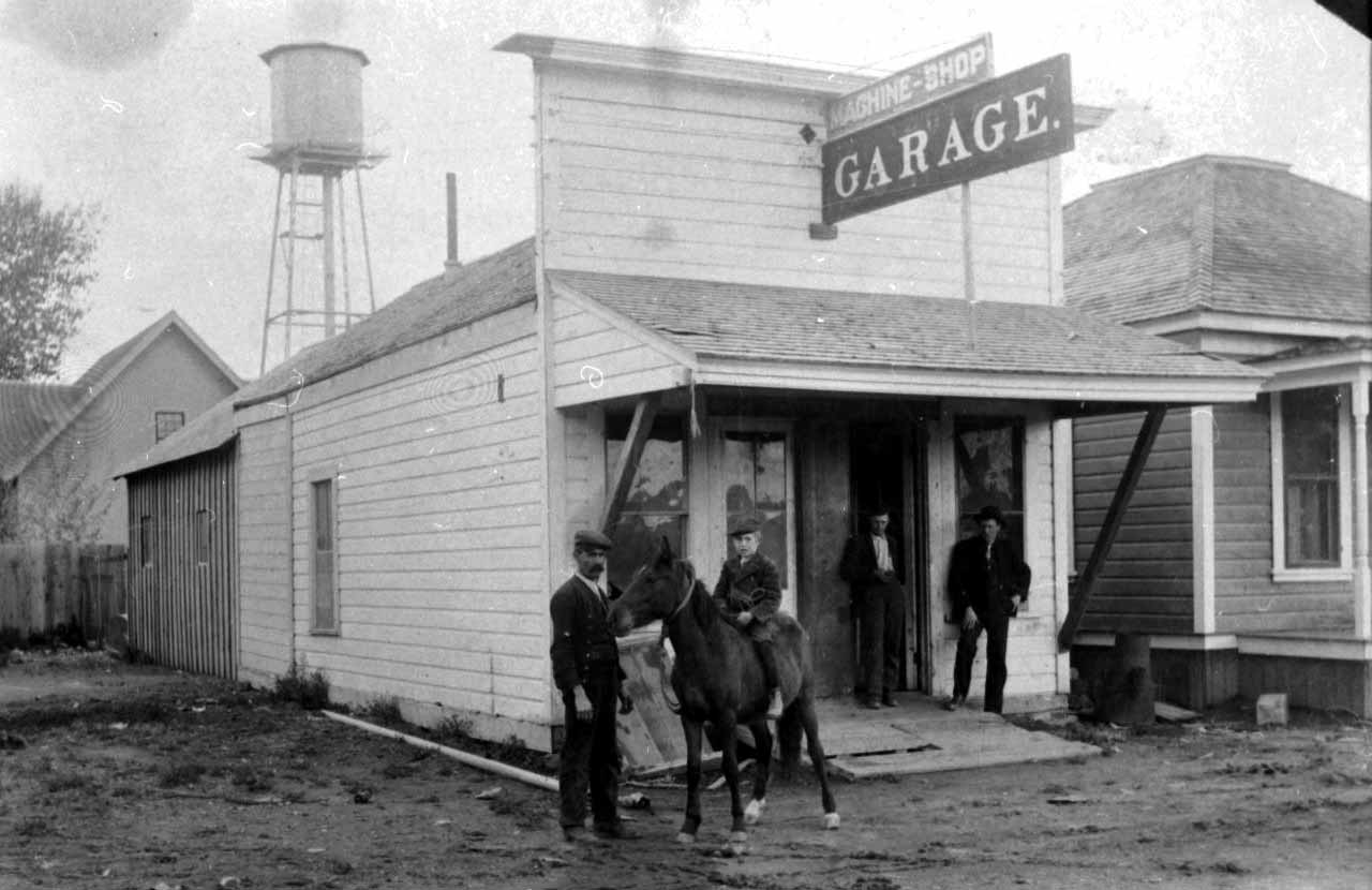 Black-and-white photo of a machine shop and garage with a horse and rider out front.