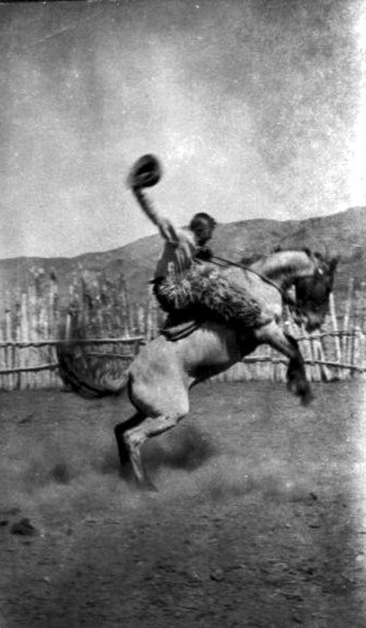 Black-and-white photo of bronc-busting rodeo rider.