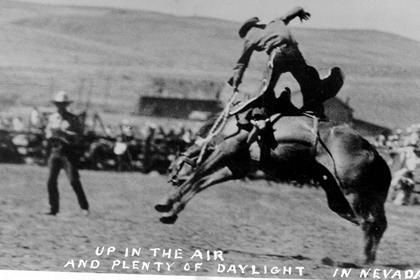 Black-and-white photo of a saddle bronc rodeo rider coming out of the saddle.