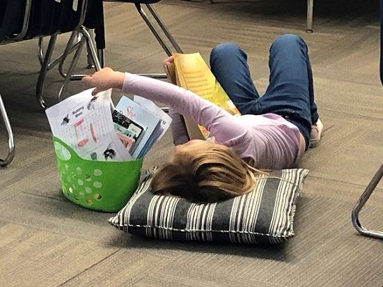 Child reclining on the floor reaches for papers